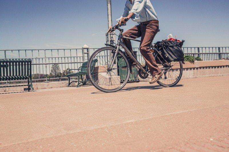 Vale a pena ter seguro de bicicleta, homem pedala em ponte