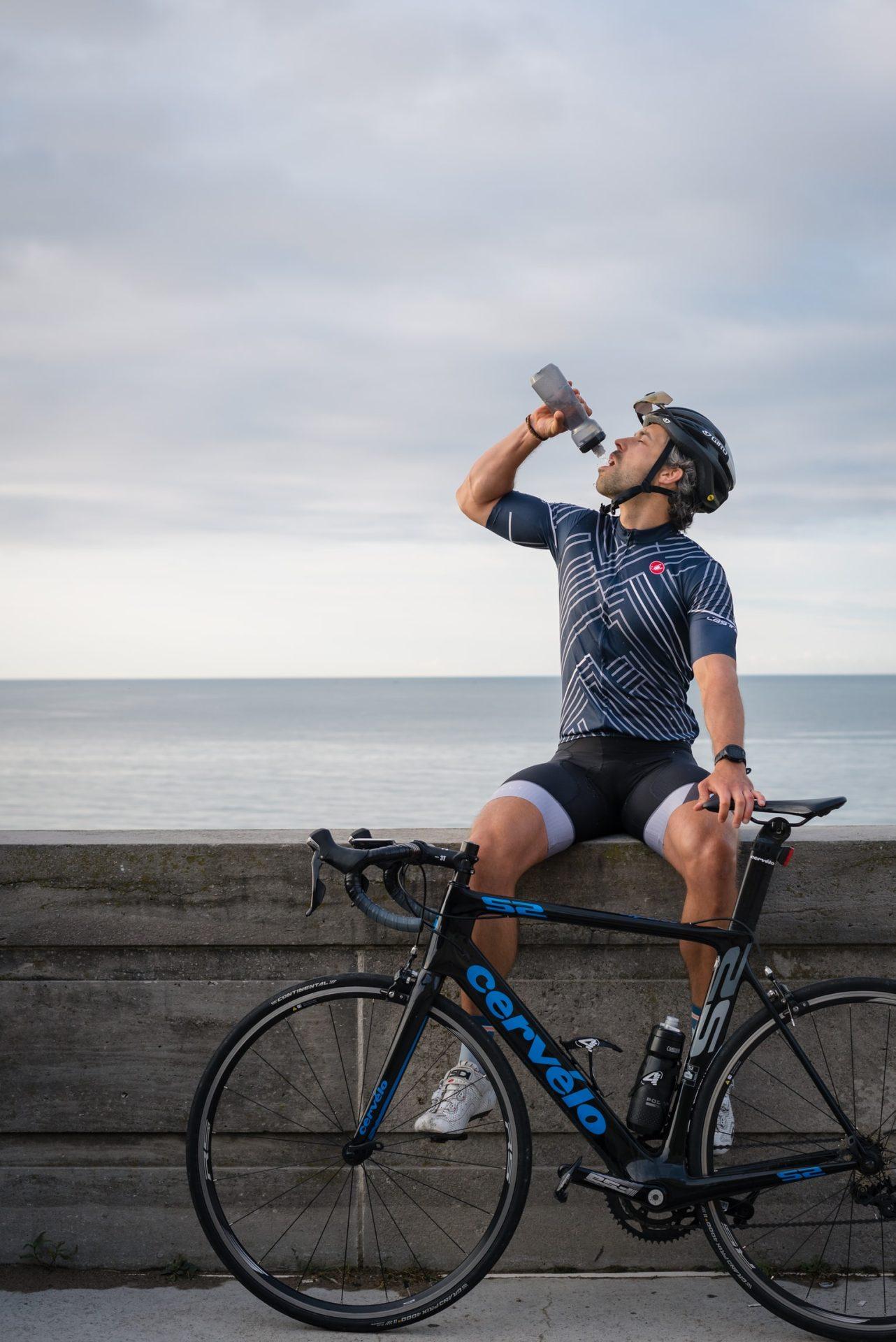 Pedalar engrossa as pernas, ciclista tomando água